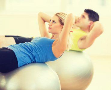 Sporters doen een fitnessoefening met een fitnessbal